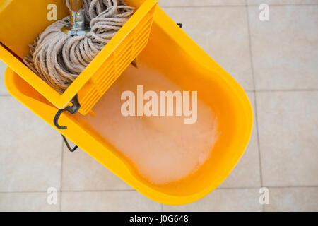 Overhead view of mop bucket on tiled floor - Stock Photo