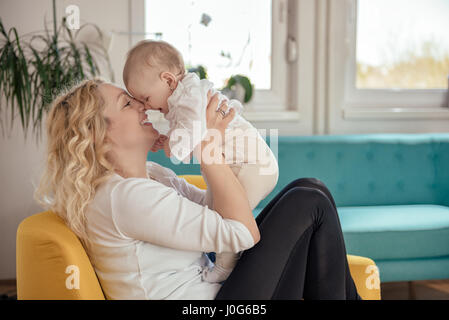 Mother and her baby head to head sitting at yellow armchair - Stock Photo