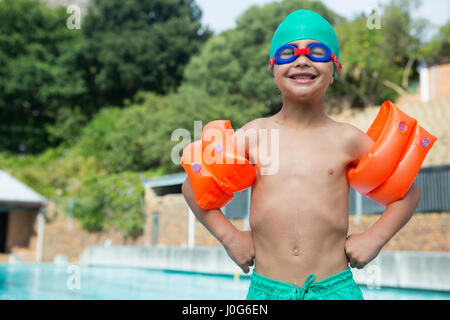 Portrait of boy wearing arm band standing at poolside - Stock Photo