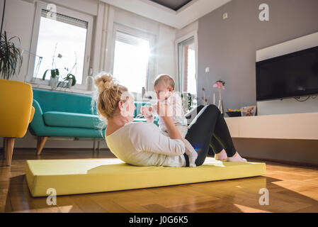 Mother Exercise With Her Baby on yellow mat At Home - Stock Photo