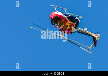 Red helicopter in the air front view, facing towards viewer on plain background performing aerobatic maneuvers, - Stock Photo