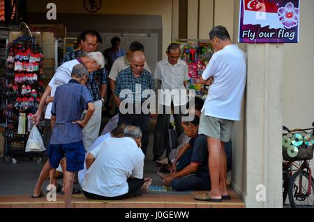 Group of Chinese men watch a game of checkers and entertain themselves in Singapore Toa Payoh neighborhood - Stock Photo