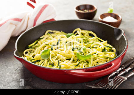Spiralized zucchini noodles in a cast iron pan - Stock Photo