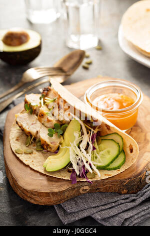 Making tacos with grilled chicken and avocado - Stock Photo