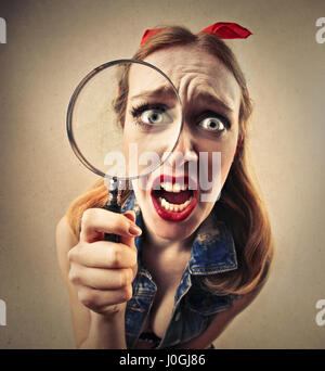 Pin-up woman with magnifying glass - Stock Photo