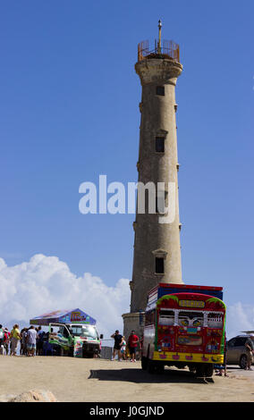 Tourists at the base of the California Lighthouse, under renovation, on the Caribbean island of Aruba.  A colorful - Stock Photo