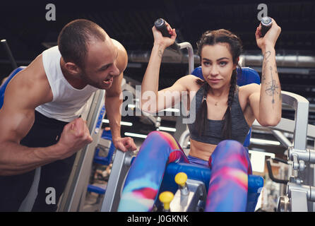 Personal trainer guding young woman at gym - Stock Photo