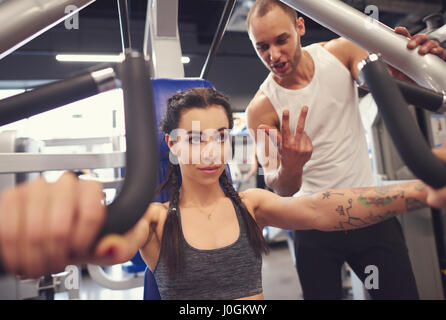 Personal trainer with woman in fitness center - Stock Photo