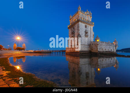 Belem Tower or Tower of St Vincent on the bank of the Tagus River during evening blue hour, Lisbon, Portugal - Stock Photo