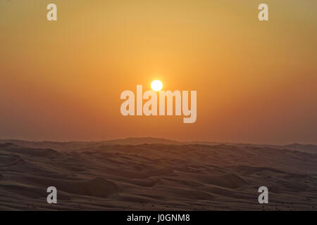 Sunset sun over the Rub' al Khali desert - Stock Photo