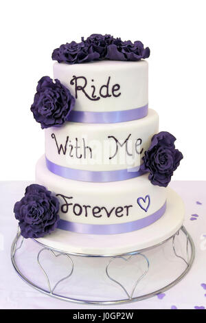 Wedding cake for bikers in three tier white icing dark purple flowers and light purple ribbons words in icing Ride - Stock Photo