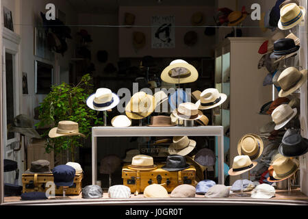 Display of men's hats - panama hats, berets, caps in clothing shop window, Lubeck, Northern Germany - Stock Photo