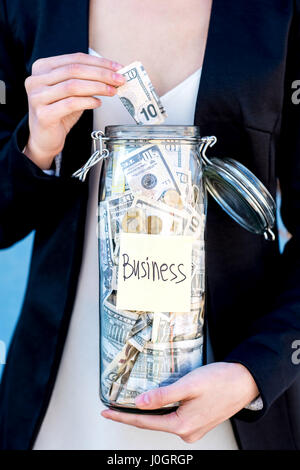 Putting money into the bottle - Stock Photo