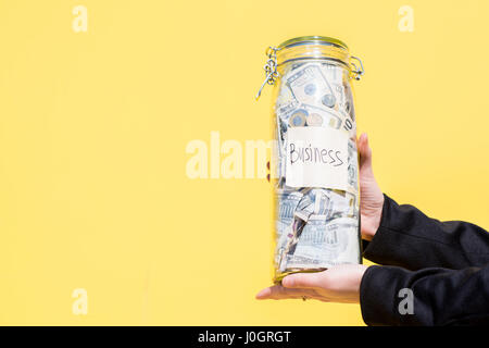 Bottle with money on the yellow background - Stock Photo