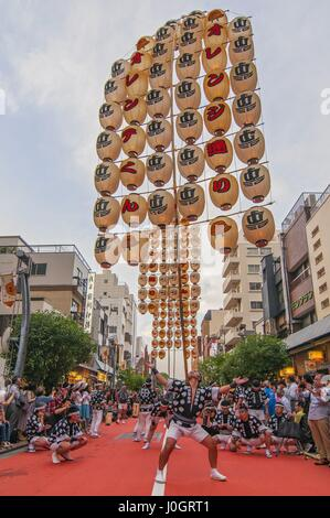 Lantern poles weighing up to 60 kilograms are balanced during the Kanto Matsuri festival in Akita Tokyo Japan - Stock Photo