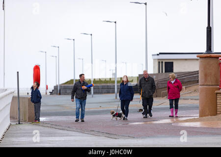 People walking along a wet and windy promenade at the popular tourist town of Rhyl in North Wales with their dogs - Stock Photo