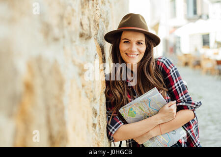 young woman, traveler, with a map and a backpack on streets of old citadel, exploring - Stock Photo