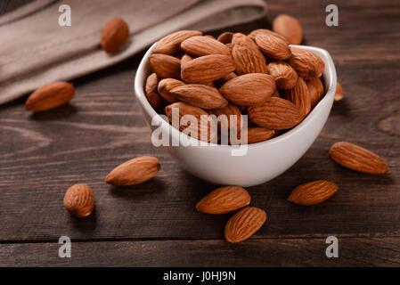 Almonds in ceramic bowl on dark wood background - Stock Photo