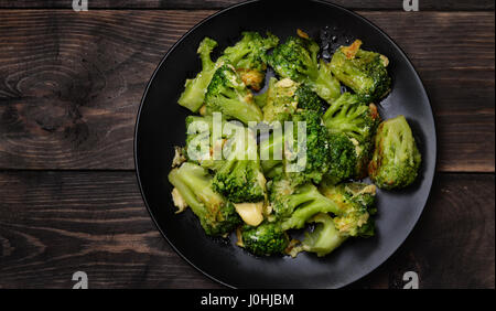 Top view of plate with roasted broccoli  on dark wooden table - Stock Photo