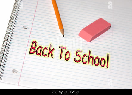 With pencil and an easer placed on top of a lined paper the phrase Back To School is written in red with black outline. - Stock Photo