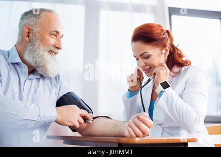 Female doctor measuring pressure of smiling senior male patient - Stock Photo