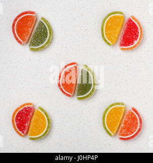 Colored sweets from marmalade in the form of slices of citrus fruits are spread out on the gray table tops in pairs. - Stock Photo
