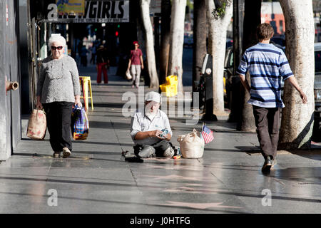 A homeless man burnishes the stars on the Hollywood walk of Fame - Stock Photo