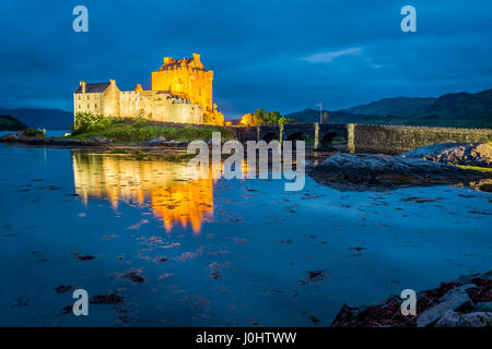 Stunning sunset over lake at Eilean Donan Castle in Scotland - Stock Photo