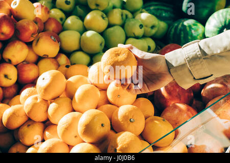 Female hand picks the oranges at the store, close-up - Stock Photo
