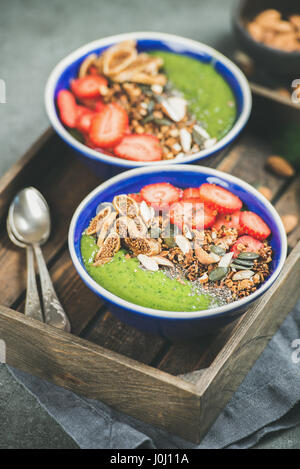 Green smoothie bowls with strawberries, granola, seeds, fruit, nuts - Stock Photo