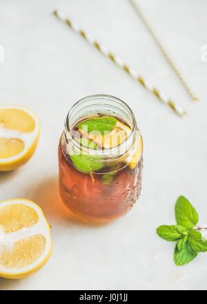 Summer cold Iced tea with lemon slices and fresh herbs - Stock Photo