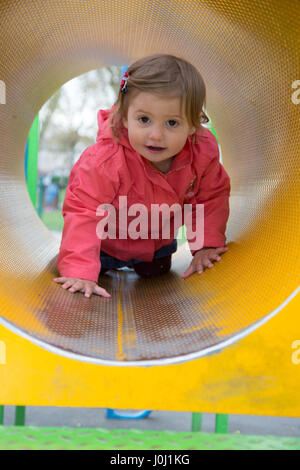 Girl toddler of 16 months in a public park playground - Stock Photo