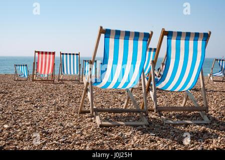 Empty traditional striped deckchairs on Brighton beach, England, UK - Stock Photo