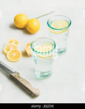 Morning detox lemon water in glasses and fresh lemons - Stock Photo
