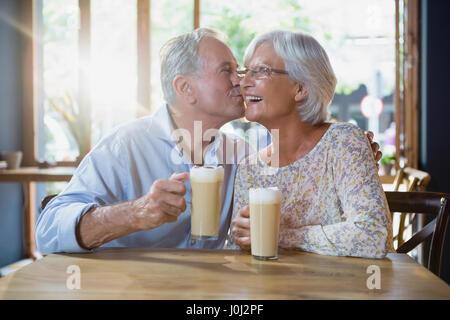Senior man kissing senior woman in café - Stock Photo
