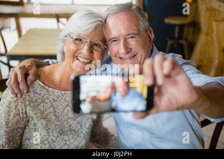 Happy senior couple taking selfie on mobile phone in café - Stock Photo