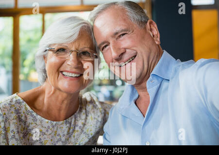 Portrait of happy senior couple sitting in café - Stock Photo
