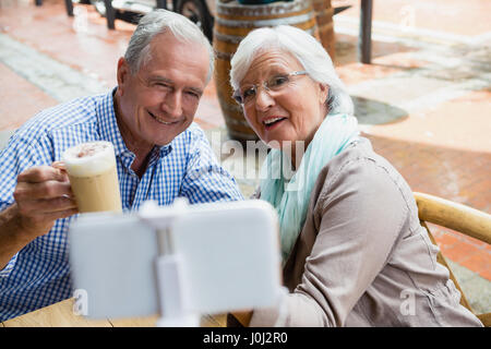 Senior couple taking selfie from mobile phone in outdoor café - Stock Photo