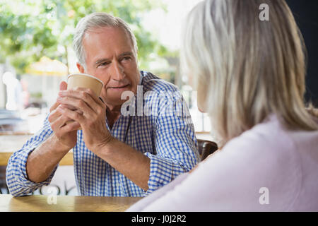 Senior couple interacting with each other in café - Stock Photo