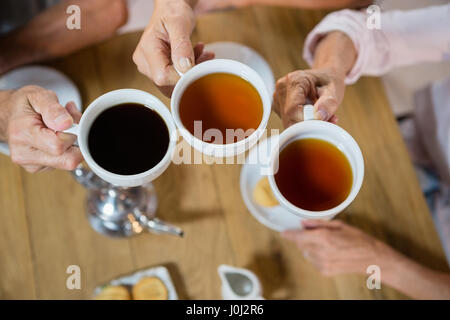 Group of senior friends toasting coffee cups in café - Stock Photo