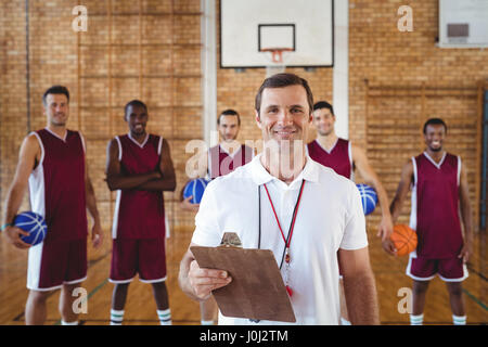 Portrait of smiling coach and basketball player standing in the court - Stock Photo