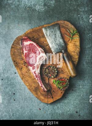 Dry aged raw beef rib eye steak on board - Stock Photo