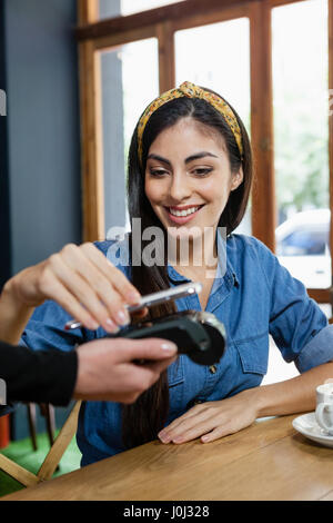 Woman making payment on credit card reader while sitting at cafe shop - Stock Photo