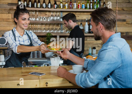 Waitress serving breakfast to man at counter in cafe - Stock Photo