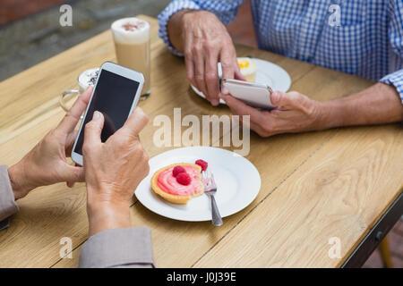 Senior couple using mobile phone in outdoor café - Stock Photo