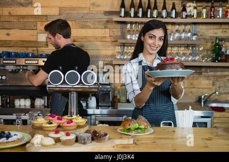 Portrait of smiling waitress holding a chocolate cake at counter in café - Stock Photo