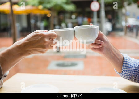 Hands of senior couple toasting coffee cups in outdoor cafe - Stock Photo