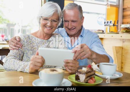 Happy senior couple using digital tablet in café - Stock Photo