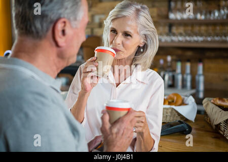Senior couple interacting with each other while having coffee in café - Stock Photo