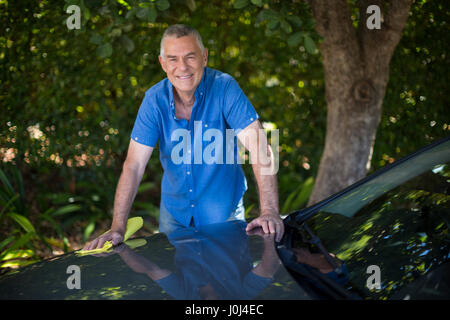 Portrait of senior man cleaning car by tree - Stock Photo